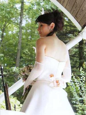 ゴールドのレースをあしらったミルク色のサテンのウェディングドレス